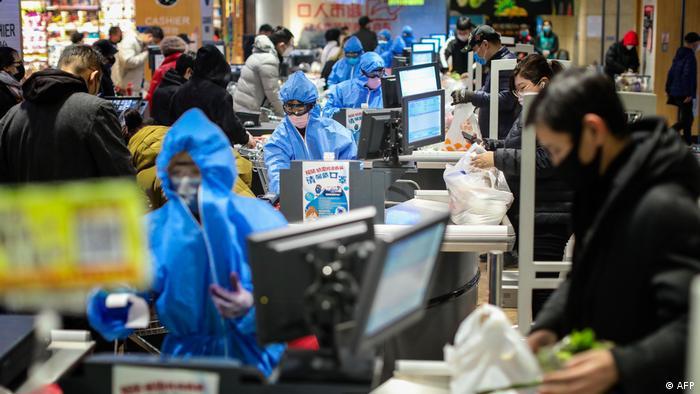 Empleados de un supermercado en China se protegen contra el coronavirus con trajes especiales y mascarillas.