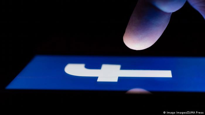 Finger about to touch facebook logo on a smartphone screen