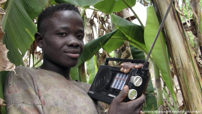Boy smiles as he holds a radio set in a banana plantation