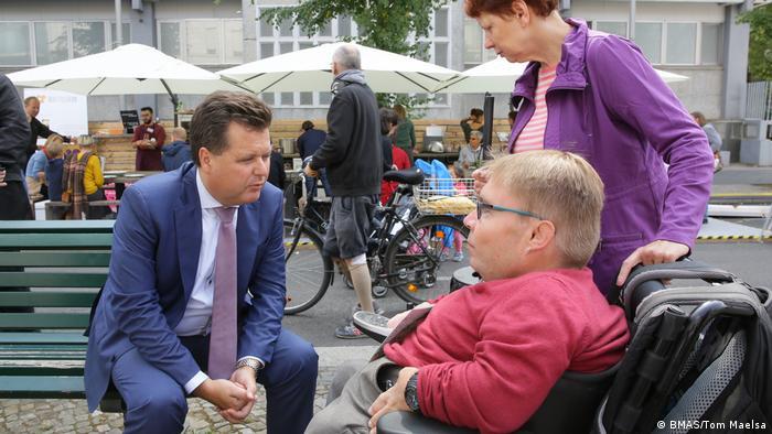 Jürgen Dusel speaking to woman in wheelchair