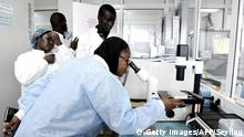Scientific staff members works in a secure laboratory, researching the coronavirus, at the Pasteur Institute in Dakar on February 3, 2020. - The Pasteur Institute in Dakar, designated by the African Union as one of the two reference centres in Africa for the detection of the new coronavirus that appeared in China, is hosting experts from 15 countries on the continent this weekend to prepare them to deal with the disease. (Photo by Seyllou / AFP) (Photo by SEYLLOU/AFP via Getty Images)
