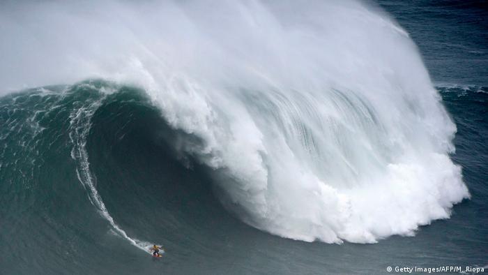 El español Axier Muniain monta una gigantesca ola en el Nazare Tow Surfing Challenge, en Nazaré, Portugal. Se trata de una competencia organizada por la Liga Mundial de Surf en la que por primera vez compiten equipos para deslizarse sobre las olas más grandes del mundo. En 2017, el brasileño Rodrigo Koxa estableció un record Guinnes al surfear una ola de 24,30 metros aquí en la costa portuguesa.