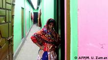 This photograph taken on February 8, 2020 shows a sex worker standing in front of her house inside a brothel area in Daulatdia in Rajbari District, 110 kms (70 miles) west of Dhaka. - Daulatdia is one of about 12 legal but frowned upon brothel areas operating in the country. (Photo by Munir UZ ZAMAN / AFP) / TO GO WITH Bangladesh-prostitution-death-religion,FOCUS by Shafiqul ALAM