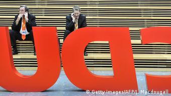 Логотип ХДС на фоне двух человек