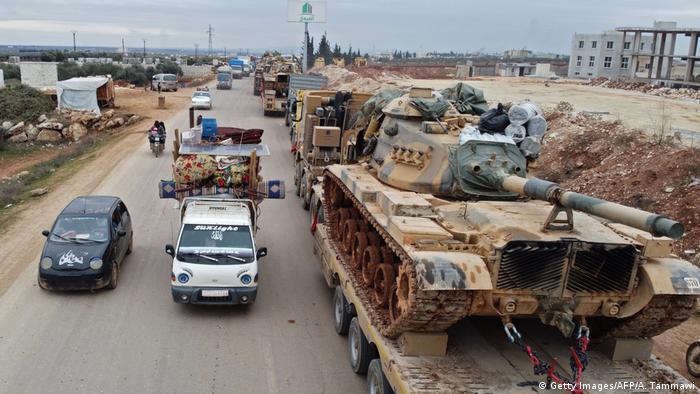 Flüchtende aus Idlib mit vollbepackten Autos auf der einen Seite, türkische Militärfahrzeuge auf der anderen