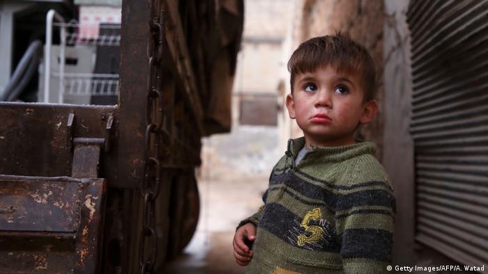 Criança síria observa seus parentes carregando pertences em caminhão antes de deixarem a cidade de Binnish, no noroeste da província de Idlib