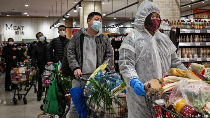 Residents wear protective masks as they line up in the supermarket on February 12, 2020 in Wuhan, Hubei province, China