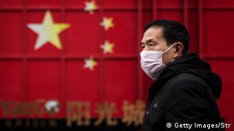Мужчина в медицинской маске и флаг Китая в городе Ухань
