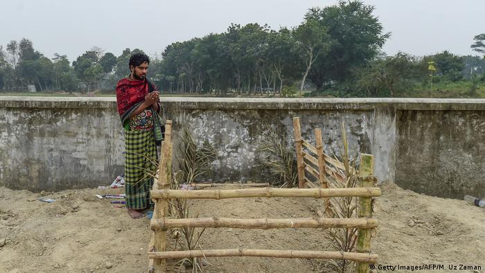 Hamida Begum's son Mukul praying in front of his mother's grave/ AFP via Getty Images
