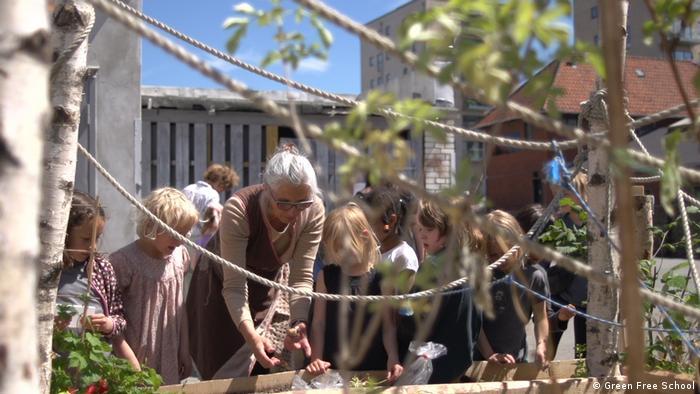 Teachers and pupils examine plants at the Green Free School in Copenhagen, Denmark