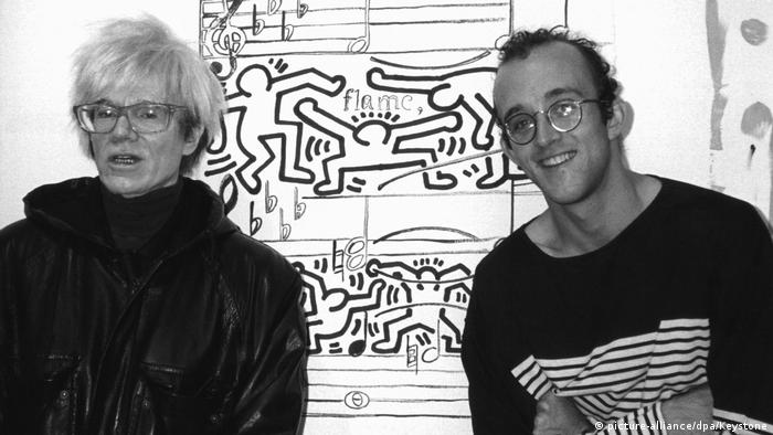 Andy Warhol and Keith Haring standing next to each other in front of a work by Haring (picture-alliance/dpa/Keystone)