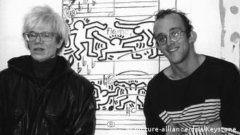 Andy Warhol und Keith Haring posieren vor einem Bild Harings (picture-alliance/dpa/Keystone)