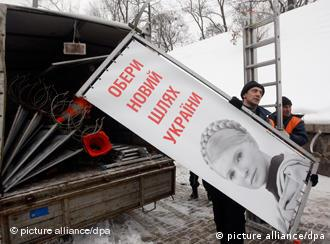 a worker removes a Tymoshenko poster