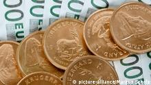 Krügerrand-Goldmünzen und Euroscheine liegen am 13.11.2014 in Hamburg auf einem Tisch. Foto: Markus Scholz | Verwendung weltweit