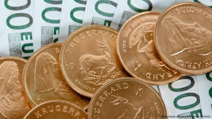 PЗолотые монеты на еврокупюрах.