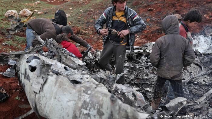 Sírios inspecionam destroços de um helicóptero militar do governo após ele ter sido abatido sobre a província de Aleppo