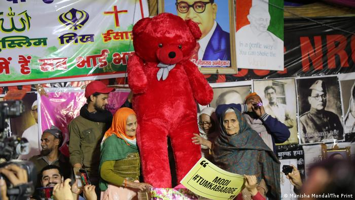 Indian protesters with a giant red teddy bear