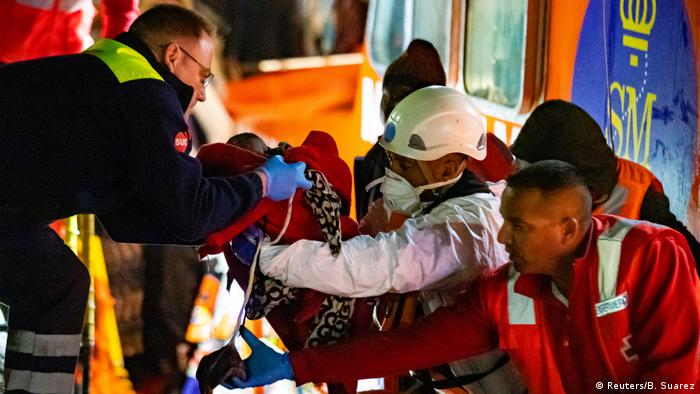 A newborn's umbilical cord and placenta are seen as it is taken away by a rescue worker from a Spanish coast guard vessel after being born at the sea near the port of Arguineguin on the island of Gran Canaria