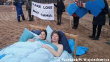 """An activist couple spent Valentine's day morning naked in bed on the site of a planned canal which Poland's ruling Law and Justice (PiS) party wants to cut across a narrow strip of land that separates its eastern coastline from the Baltic Sea. """"Make love not canal,"""" said a banner held by other activists standing by the bed on the Vistula Spit, a heavily wooded sandbank 55 km (35 miles) long but less than 2 km (1.25 miles) wide, enclosing a coastal lagoon."""