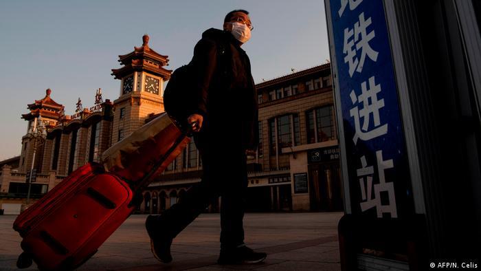 Мужчина в медицинской маске везет чемодан к зданию вокзала Пекина