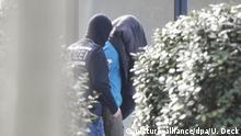 Ein mutmaßliches Mitglied einer rechten Terrorzelle wird von einem vermummten Polizisten aus dem BGH in Karlsruhe gebracht