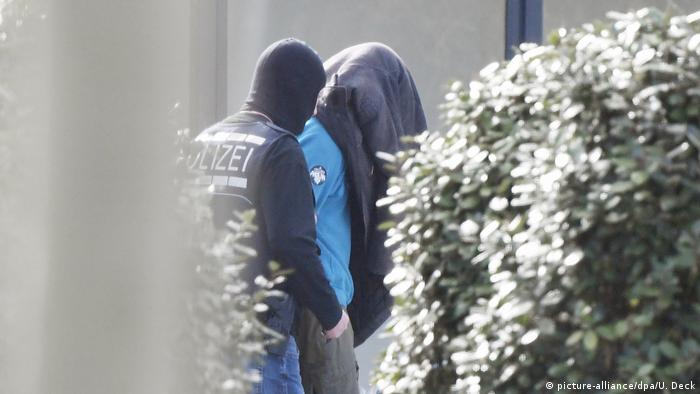 A policeman walks behind a suspect in Karlsruhe