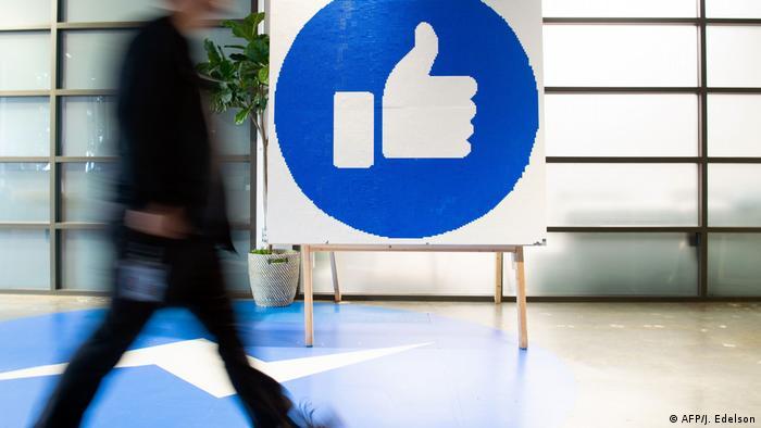 Pessoa anda em frente a uma placa com o símbolo de curtir do Facebook