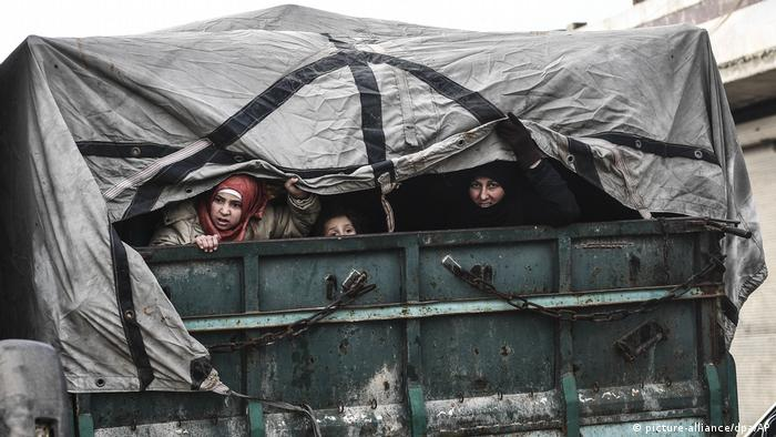 Civilians fleeing Idlib in the back of a truck