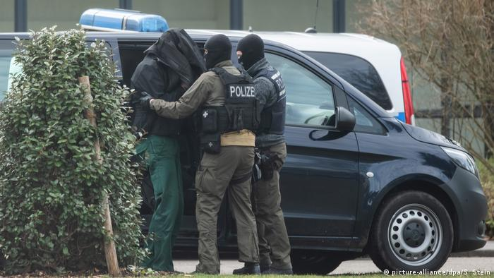 Suspect with coat over head being put in a police van (picture-alliance/dpa/S. Stein)