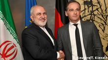 Iranian Foreign Minister Javad Zarif shakes hands with German Foreign Minister Heiko Maas