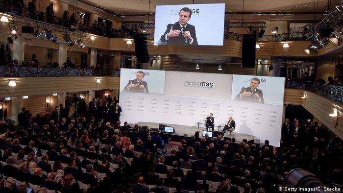 France's President Emmanuel Macron (at left on podium) is displayed on screens as he talks with the chairman of the Munich Security Conference Wolfgang Ischinger during the 56th Munich Security Conference (MSC) on February 15, 2020