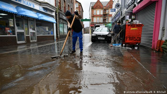 Man sweeps flood waters in streets