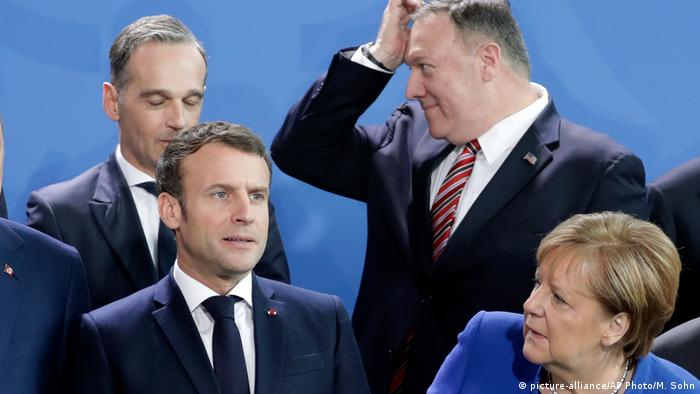 Various European politicians stand next to each other and make gestures and faces