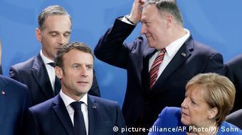 Emmanuel Macron, Angela Merkel, Heiko Mass und Mike Pompeo stehen zusammen. Alle zeigen eine andere Gesichtsmimik
