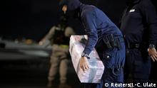 A police officer carries a package containing cocaine seized during an operation in the Caribbean, at the air base of the Ministry of Security in Alajuela, Costa Rica, February 15, 2020. REUTERS/Juan Carlos Ulate