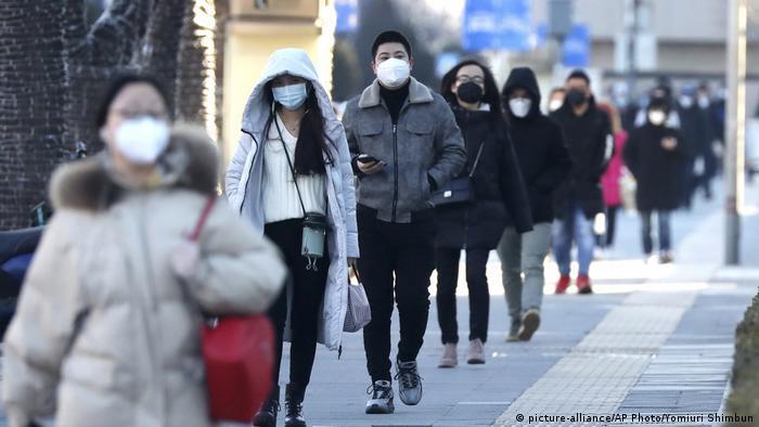Personas caminando por la calle usando máscaras protectoras.