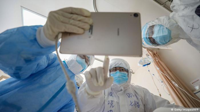 Petugas medis di rumah sakit di Wuhan melihat ke monitor saat tengah memeriksa pasien COVID-19