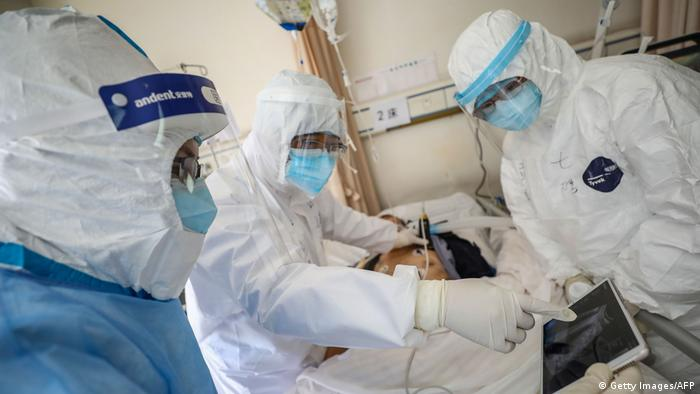 Medical personnel in protective suits surrounding a patient on a bed (Getty Images/AFP)