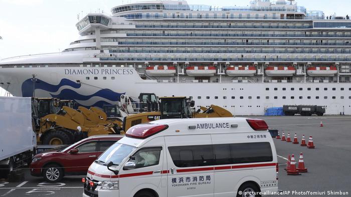 Ambuância estacionada no porto de Yokohama, no Japão, com carro vermelho atrás. Ao fundo, vista do navio de cruzeiro Diamond Princess, cujos passageiros estão sendo evacuados após 14 dias de quarentena a bordo do navio com cerca de 3,7 mil ocupantes