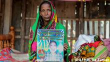 In this photograph taken on November 11, 2019, Bangladeshi mother-of-four Mosammat Rashida, whose husband was killed by a Bengal tiger a decade ago while he was collecting honey, holds a portrait of her husband during an interview with AFP at her house in Shyamnagar. - Women whose husbands have been killed by the Bengal tiger are shunned in Bangladesh by superstitious villagers who believe they are bad omens who should be blamed for their spouse's untimely death. (Photo by Munir UZ ZAMAN / AFP) / TO GO WITH Bangladesh-women-animal-environment,FOCUS by Sam Jahan