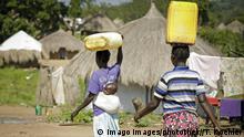 Uganda Junge Frauen transportieren Kanister mit Wasser auf ihrem Kopf