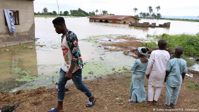 Nigeria floods with people standing by the river