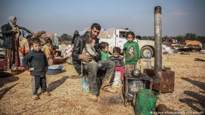 A family with six children sit in front of a makeshift stove in a field