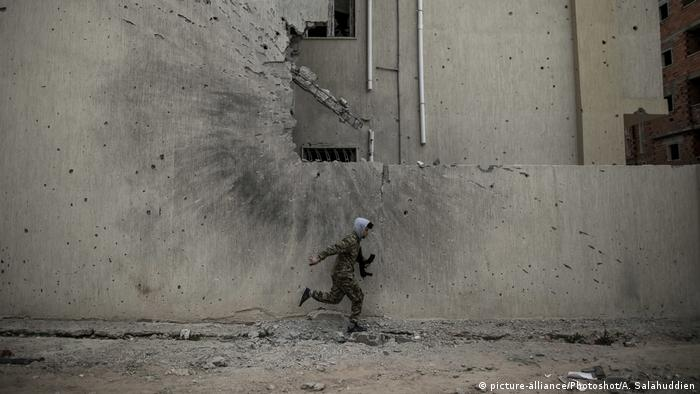 A soldier running to take cover from snipers on a front line in Tripoli, Libya
