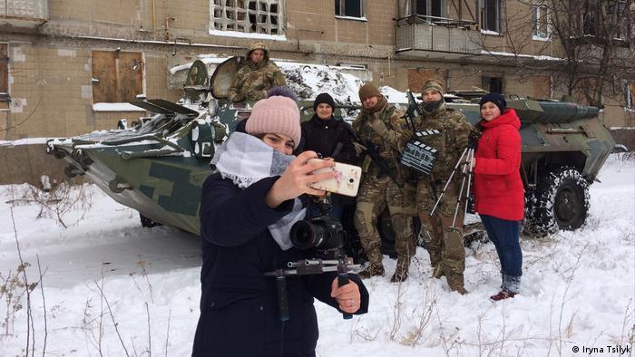 Myroslava Trofymchuk (vorne), Anna Gladka (Mitte), und Anastasiia Trofymchuk (rechts) mit ukrainischen Soldaten bei den Dreharbeiten für ihren Familienfilm
