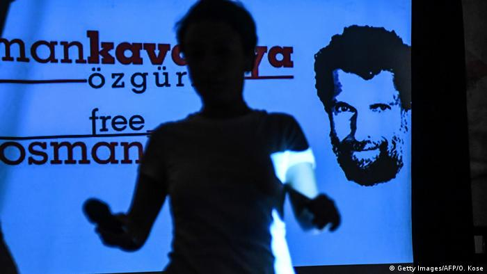 Osman Kavala's head appears on a screen demanding his release