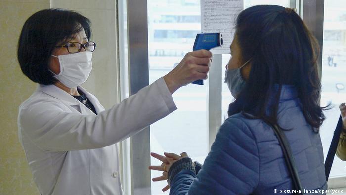 Mulher tem sua temperatura verificada antes de entrar em um banho público em Pyongyang