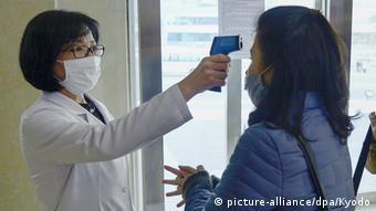 Женщине измеряют температуру тела перед посещением бассейна в Пхеньяне