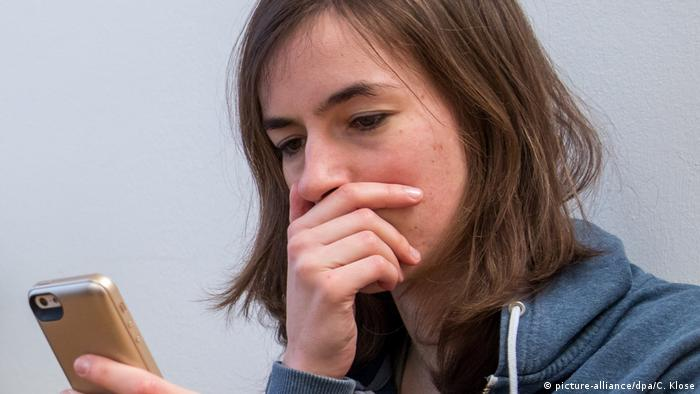 A woman looking at a smartphone in a state of shock