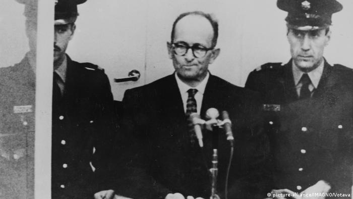 Adolf Eichmann flanked by policemen at his trial in Israel
